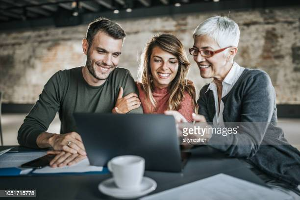 Happy couple and their real estate agent using laptop in the office.