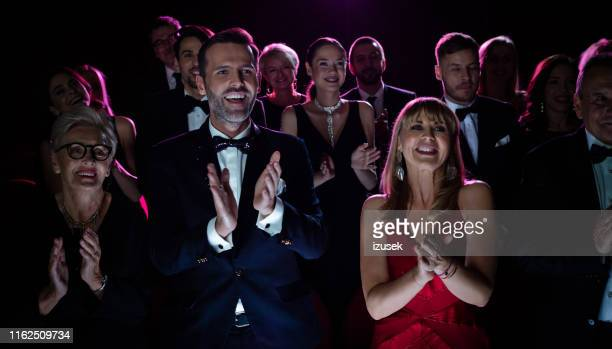 happy couple applauding while watching opera - applauding stock pictures, royalty-free photos & images