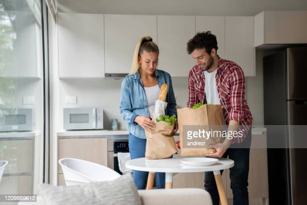 happy couple arriving home after grocery shopping - arrival stock pictures, royalty-free photos & images