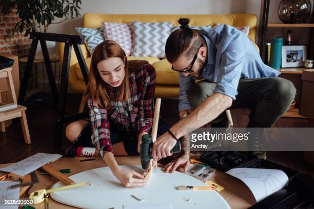 happy couple assembling new furniture - building activity stock pictures, royalty-free photos & images