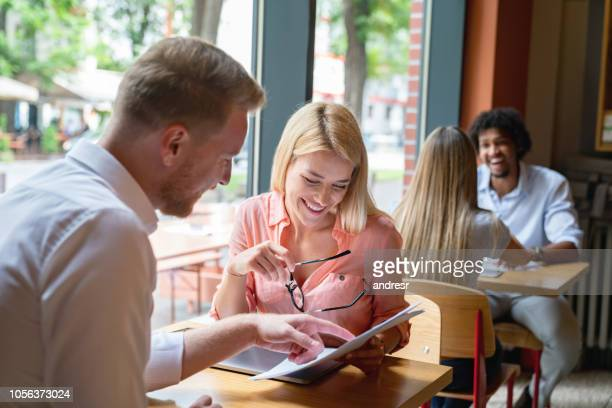 happy couple at a restaurant looking at the menu - menu stock pictures, royalty-free photos & images
