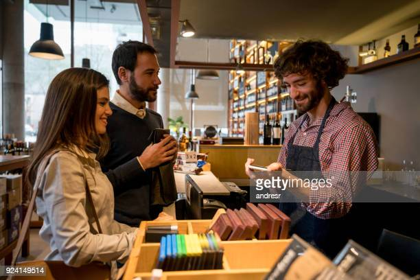 happy couple at a wine store checking out and salesman processing their payment through a smartphone - liquor store stock pictures, royalty-free photos & images