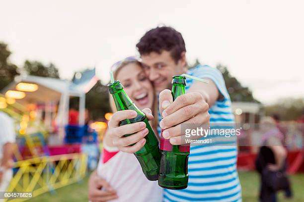 Happy couple at fun fair drinking soft drinks