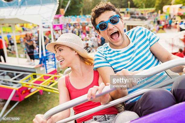 Happy couple at fun fair riding roller coaster