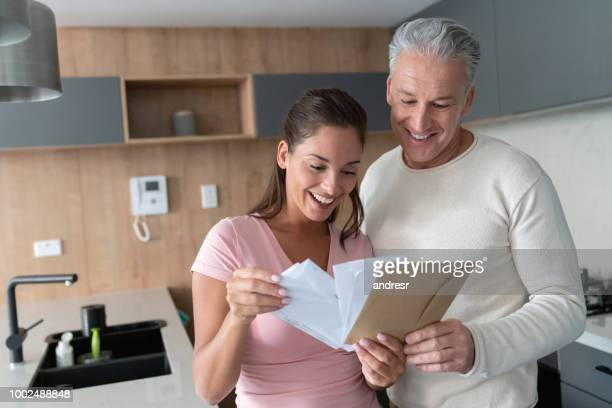Happy couple at home checking their mail