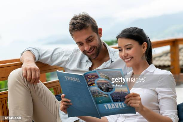 happy couple at home reading a travel magazine - magazine publication stock pictures, royalty-free photos & images