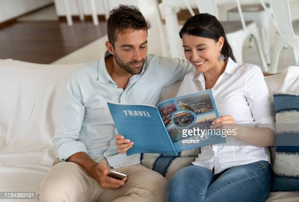 happy couple at home reading a travel magazine - flyer leaflet stock pictures, royalty-free photos & images