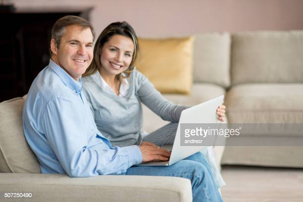 Happy couple at home with a laptop