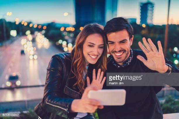 Gelukkige paar op de brug die genieten van een video-oproep