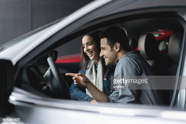 Happy couple at the dealership looking at the interior of a car