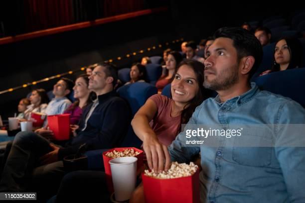 glückliches paar bei den filmen und frau stehlen popcorn - filmindustrie stock-fotos und bilder