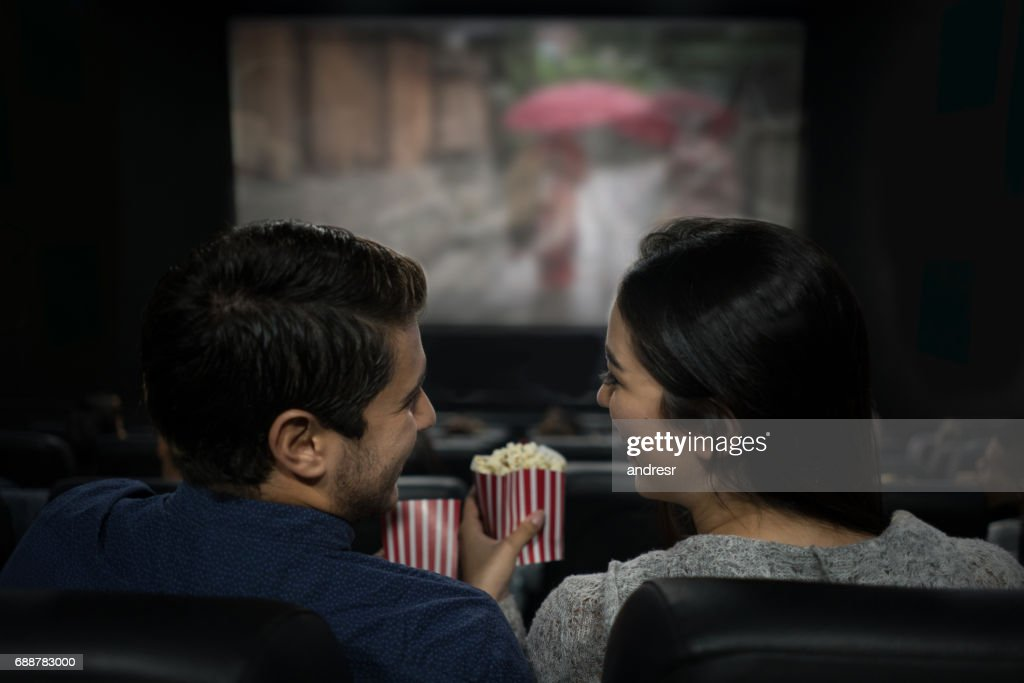 Happy couple at the movies eating popcorn and having fun : Stock Photo