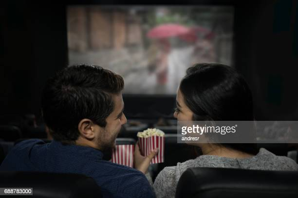 happy couple at the movies eating popcorn and having fun - industria cinematografica foto e immagini stock