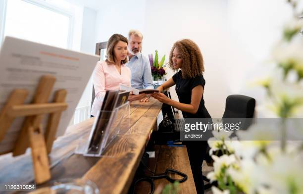 happy couple at the spa talking to the manager - hotel stock pictures, royalty-free photos & images