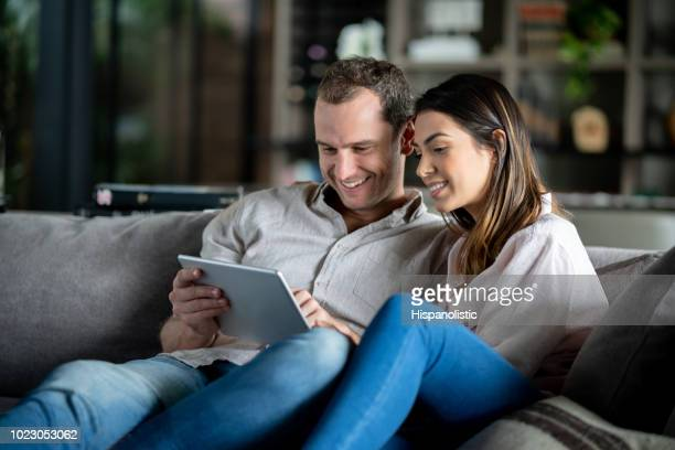Happy couple at their apartment relaxing on couch and watching videos on tablet