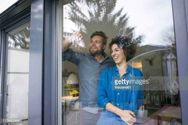 happy couple behind window at home looking out - 40 44 jahre stock-fotos und bilder