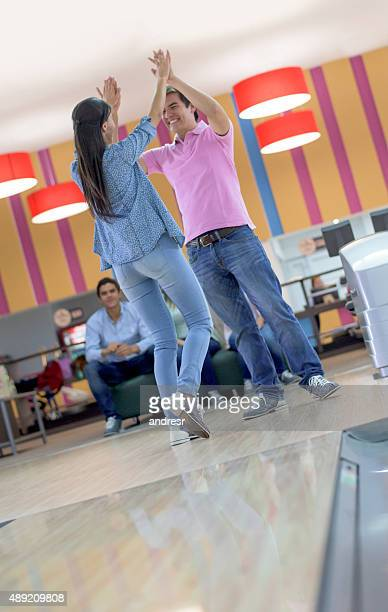 Happy couple bowling and celebrating a strike