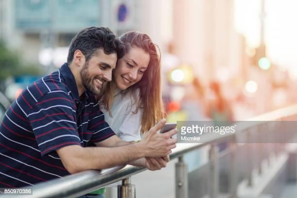 Pareja feliz viendo y viendo juntos en el teléfono