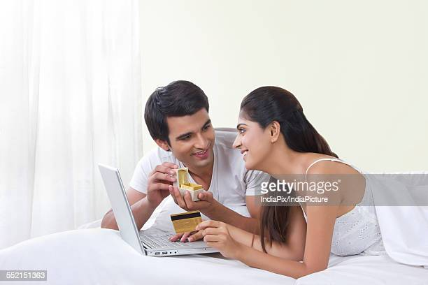 Happy couple buying ring online with credit card in bed