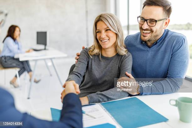 happy couple came to an agreement with their financial advisor in the office. - lease agreement stock pictures, royalty-free photos & images