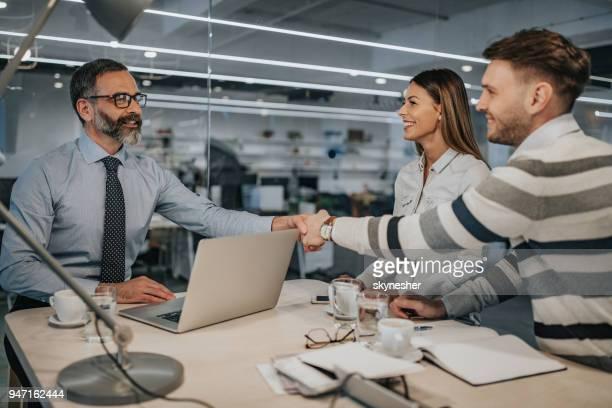 gelukkige paar kwam tot een overeenkomst met hun verzekeringsagent in het kantoor. - bedrijven financiën en industrie stockfoto's en -beelden