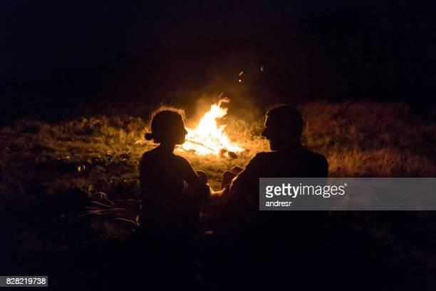 glückliches paar camping und lagerfeuer entspannen - holzfeuer stock-fotos und bilder
