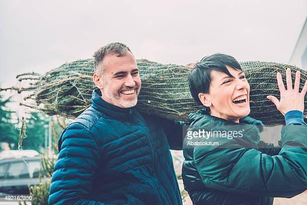 Glückliches Paar tragen Christmas Tree auf den Schultern, Europa