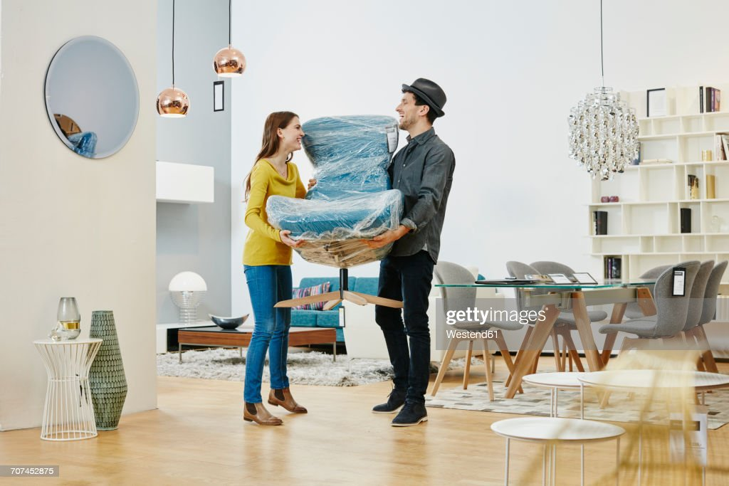 Happy couple carrying new arm chair out of furniture store : Foto de stock