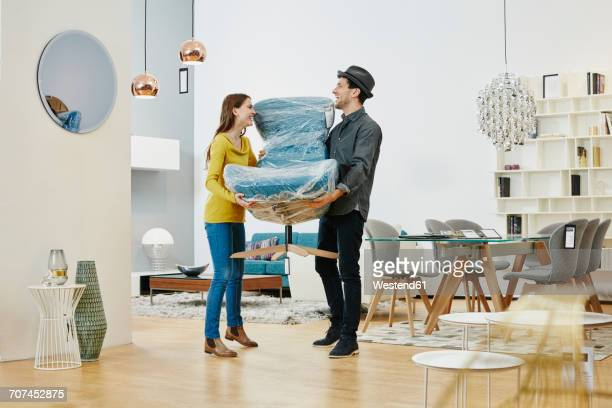 happy couple carrying new arm chair out of furniture store - hausdekor stock-fotos und bilder