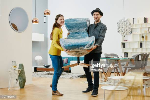 Happy couple carrying new arm chair out of furniture store