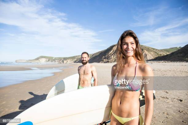 Happy couple carrying surfboards on the beach