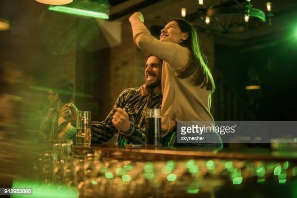 glückliches paar zusehen ein fußballspiel in einer bar feiern. - club football stock-fotos und bilder