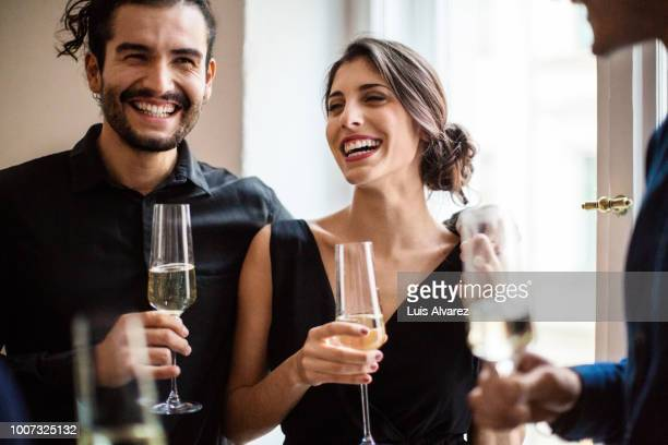 happy couple champagne flutes during dinner party - elegantie stockfoto's en -beelden