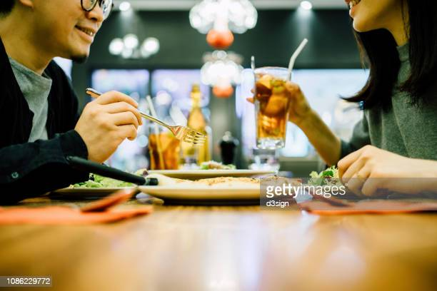 happy couple chatting and enjoying meal in a restaurant - romantic dinner stock pictures, royalty-free photos & images