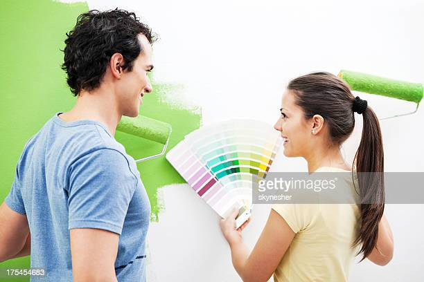 Happy couple choosing color for the wall