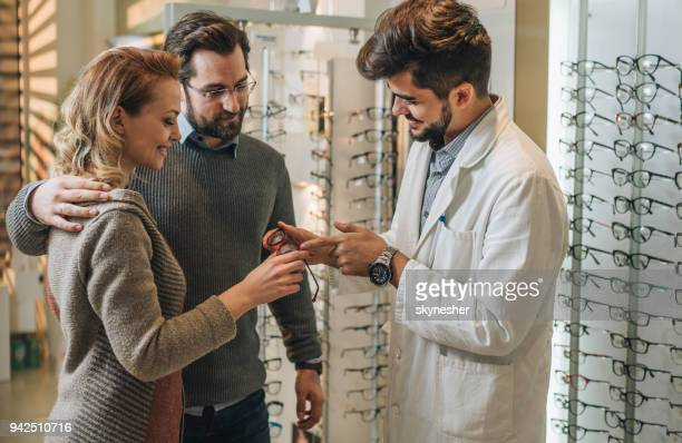happy couple choosing new eyeglasses with help of young optician. - optician stock pictures, royalty-free photos & images
