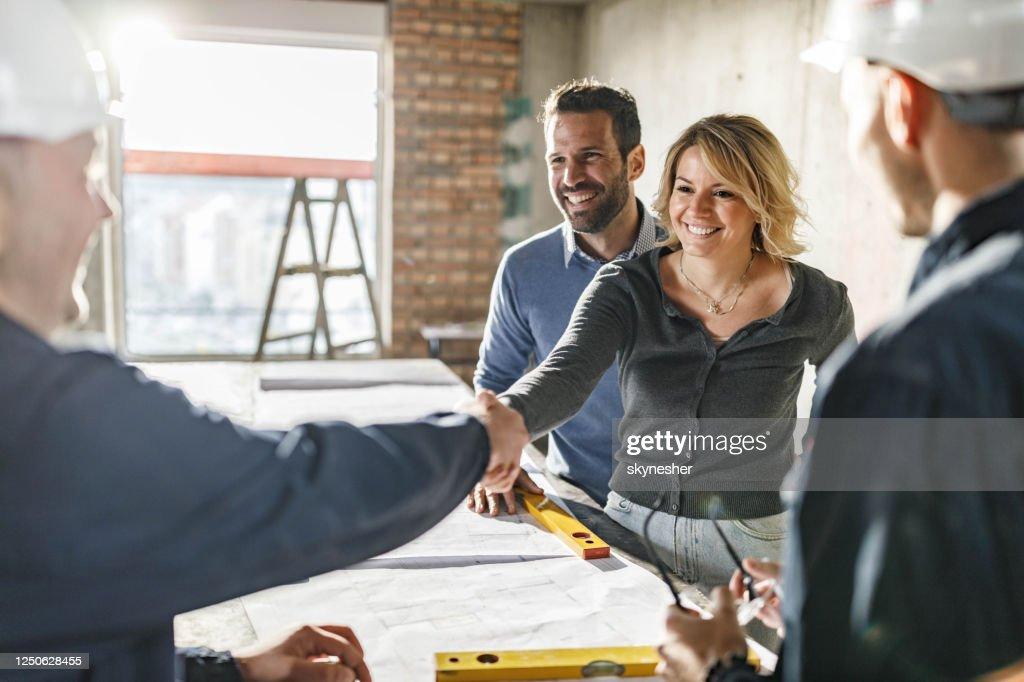 Het gelukkige paar sloot een overeenkomst met handarbeiders bij bouwplaats. : Stockfoto