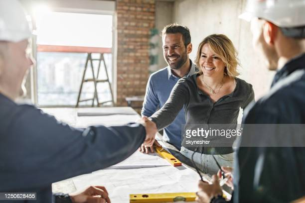 happy couple closed a deal with manual workers at construction site. - building contractor stock pictures, royalty-free photos & images