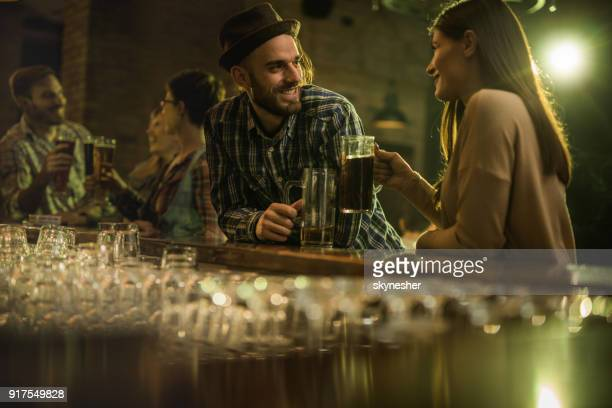 happy couple communicating at bar counter during the night out. - flirtare foto e immagini stock