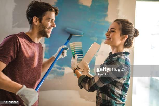 glückliches paar kommunikation bei der auswahl der richtigen farbe für ihre wand. - malen stock-fotos und bilder