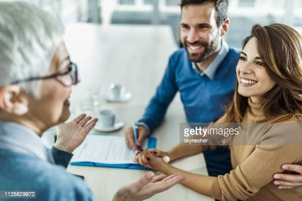 happy couple communicating with their financial advisor on a meeting in the office. - financial advisor stock pictures, royalty-free photos & images