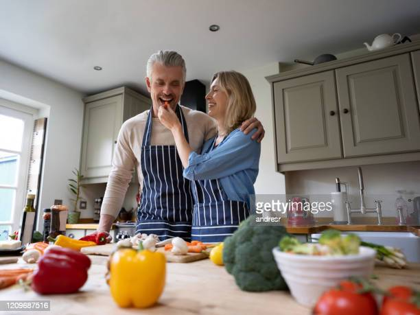happy couple cooking together and wife feeding husband a bite - wife stock pictures, royalty-free photos & images