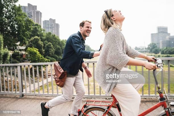 happy couple crossing a bridge with bicycle and by foot - atividade romântica - fotografias e filmes do acervo