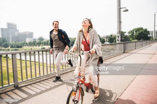 happy couple crossing a bridge with bicycle and by foot - rennen körperliche aktivität stock-fotos und bilder