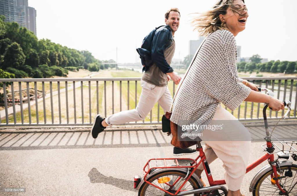 Happy couple crossing a bridge with bicycle and by foot : Stockfoto