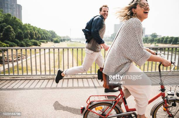 happy couple crossing a bridge with bicycle and by foot - radfahren stock-fotos und bilder