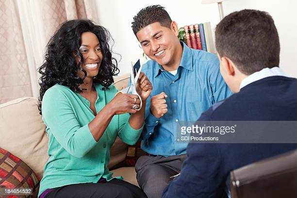 Happy couple cutting up their credit cards with financial counselor