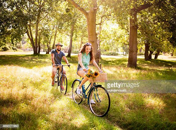 Happy couple cycling together in summer in a park
