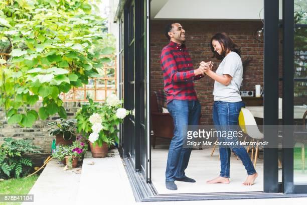 Happy couple dancing in kitchen seen from doorway