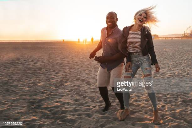 happy couple dancing on the beach - santa monica stock pictures, royalty-free photos & images